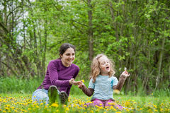 Mother and daughter in the field of dandelions Stock Image
