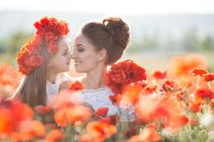 Beautiful mother and her daughter playing in spring flower field. Mother and daughter into a field of poppies.Beautiful mother and her daughter playing in spring royalty free stock images