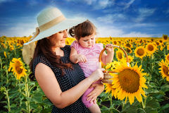 Mother with daughter on the field with sunflowers. Happy family in a field of sunflowers stock photo