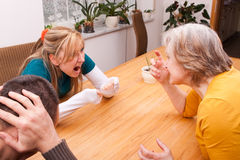 Mother and daughter fight, man keeps ears Royalty Free Stock Photos