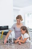 Mother and daughter filling pot with water Stock Photo