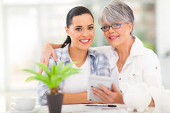 Mother daughter finances. Happy senior mother helping daughter calculate her finances Stock Photo