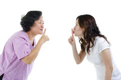 Mother and daughter finger on lips Royalty Free Stock Images