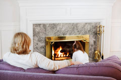 Mother & daughter by the fire Stock Photo