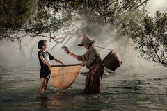 Mother and daughter are fishing at a river in the countryside. Stock Photos