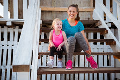 Mother and daughter in fitness gear sitting on beach hut steps Royalty Free Stock Photos