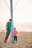 Mother and daughter in fitness gear standing by flagpole Royalty Free Stock Photos