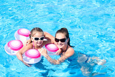 Mother and daughter floating in the swimming pool Royalty Free Stock Photography