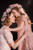 Mother and daughter in floral wreaths hugging and touching foreheads. Happy mother and daughter in floral wreaths hugging and touching foreheads Royalty Free Stock Photo