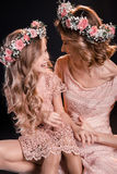 Mother and daughter in floral wreaths looking at each other and laughing. Happy mother and daughter in floral wreaths looking at each other and laughing Stock Image