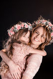 Mother and daughter in floral wreaths and pink dresses hugging. Happy mother and daughter in floral wreaths and pink dresses hugging Stock Images