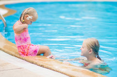 Mother and daughter with flower behind ear have fun at pool side Stock Photo
