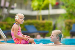 Mother and daughter with flower behind ear have fun at pool side Stock Photos