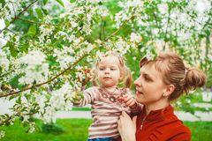 Mother and daughter in flower garden. Close up portrait of a joyful mother and daughter relaxing together in a beautiful spring field of grass and flowers Stock Photography