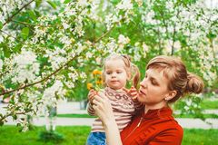 Mother and daughter in flower garden. Close up portrait of a joyful mother and daughter relaxing together in a beautiful spring field of grass and flowers Stock Image