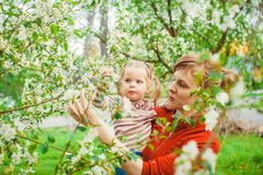 Mother and daughter in flower garden. Close up portrait of a joyful mother and daughter relaxing together in a beautiful spring field of grass and flowers Royalty Free Stock Photo