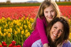 Mother and Daughter with flowers. A Mother and her Daughter in front of a colorful field of Tulips Royalty Free Stock Photography