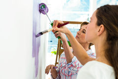 Mother and daughter focused on painting Royalty Free Stock Images