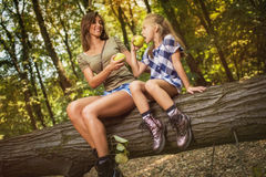 Mother And Daughter In The Forest. Beautiful young mother and her daughter sitting on fallen tree in the forest and enjoying. They looking at each other and eat Royalty Free Stock Photo