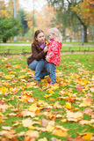 Mother and daughter gathering leaves Royalty Free Stock Photography