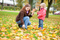 Mother and daughter gathering leaves in park Royalty Free Stock Photos
