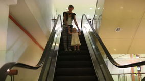 Mother and Daughter Get down the Escalator. Young mother and small blonde daughter get down the escalator in trade center stock video footage