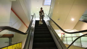 Mother and Daughter Get down the Escalator. Young mother and small blonde daughter get down the escalator in trade center stock video
