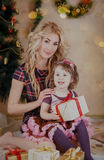 Mother and daughter with gift-box near Christmas tree Stock Photos