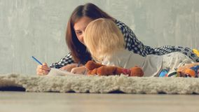 Mother and daughter girl draws a picture with pencils. Mother hugs and kisses baby. stock video footage