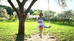 Mother with daughter girl swinging on swing in blooming tree garden at spring stock video