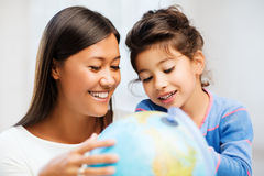 Mother and daughter with globe Stock Photos