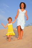 Mother with daughter go on sand Stock Image