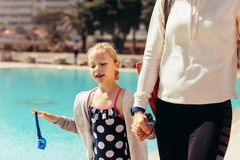 Mother and daughter going home after swimming. Girl in swimsuit walking with mother at poolside. Mother and daughter after swimming going home royalty free stock images