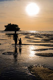 Mother with daughter going to the beautiful colorful sunset near. The small exotic island with palms Stock Photos