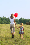 Mother and daughter going to mowed grass. View from back. Royalty Free Stock Photo