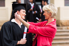 Mother daughter graduation. Happy middle aged mother hugging her daughter at graduation ceremony royalty free stock photo