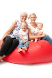 Mother daughter and grandchildren on a red sofa Stock Photo