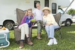Mother, Daughter And Granddaughter Outside RV Home. Portrait of little girl with mother and grandmother outside RV home Stock Photo
