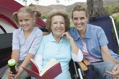 Mother, Daughter And Granddaughter Reading Outside Tent Royalty Free Stock Photo