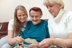 Mother, daughter and grandma looking at photos Stock Photography