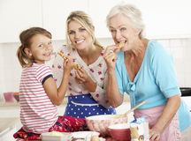 Mother,Daughter And Grandmother Baking In Kitchen Stock Image