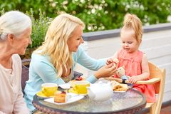 Mother, daughter and grandmother eating at cafe Royalty Free Stock Images