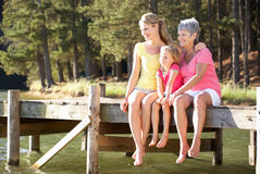 Mother,daughter and grandmother sat by lake. Mother,daughter and grandmother sitting by lake smiling off camera