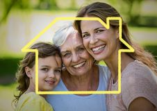 Mother, daughter and grandmother smiling together in the park with house outline. DIgital composite image of mother, daughter and grandmother smiling together in royalty free stock photo
