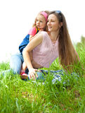 Mother and daughter  in grass. Mother and her curly daughter in grass Stock Photography