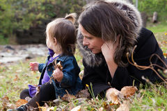 Mother and daughter in grass with autumn foliage. A close up of a mother and a toddler daughter in the grass with autumn foliage Royalty Free Stock Image