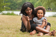 Mother and daughter on the grass. Pregnant mother and her daughter are having fun stock photo