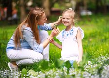 Mother with daughter in green blooming summer park on meadow collect flowers. Mother with daughter in the green blooming summer park on the meadow collect royalty free stock photos