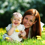 Mother and daughter on the green grass Stock Photos