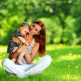 Mother and daughter on the green grass Royalty Free Stock Photos